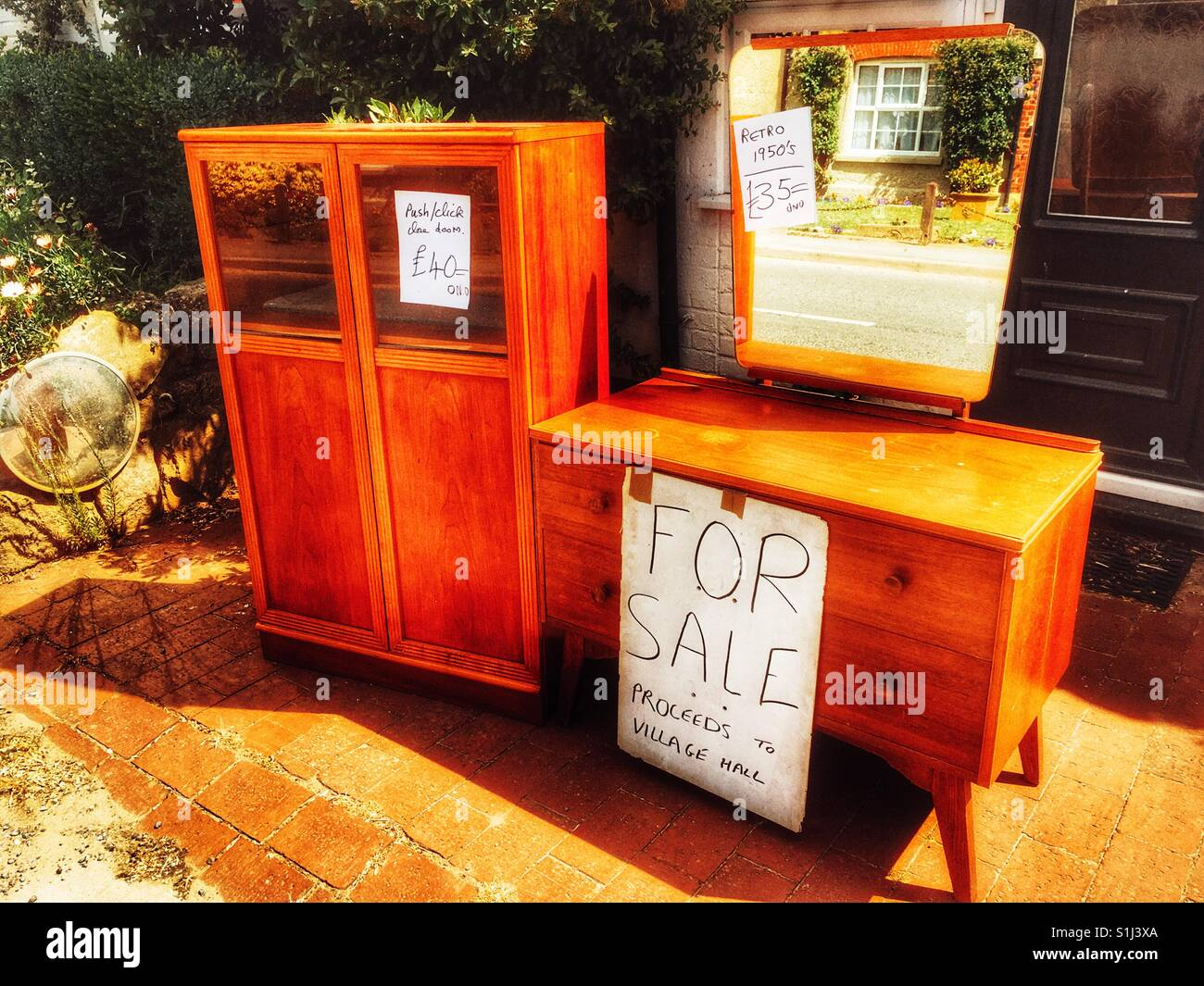 Secondhand furniture for sale outside house - Stock Image