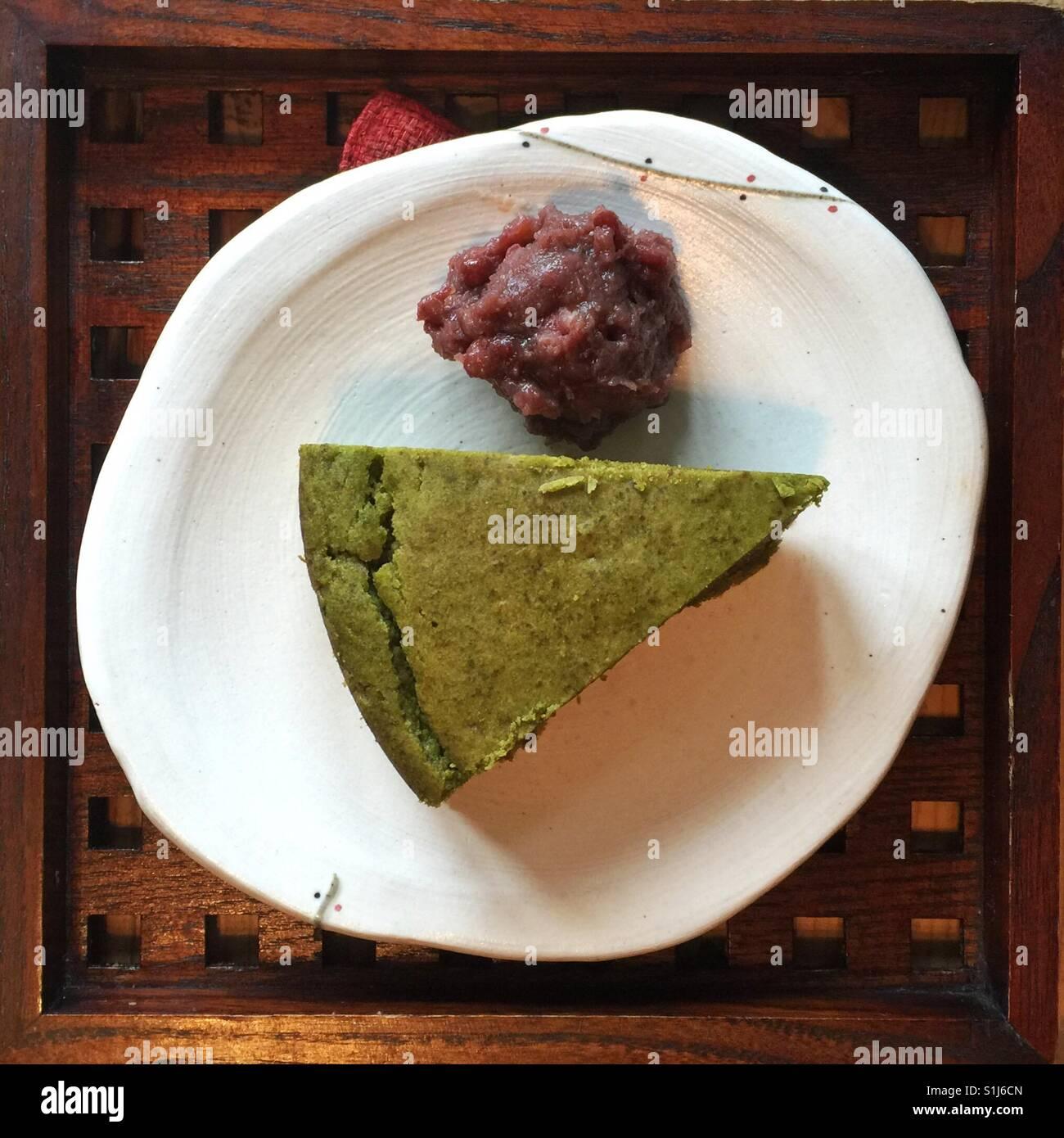 Japanese green matcha tea cake on handmade ceramic plate - Stock Image