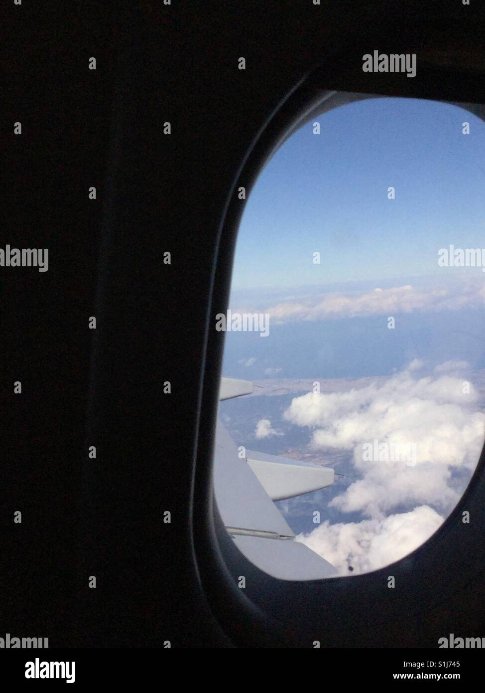 White fluffy clouds and blue sky out of aeroplane window with wing - Stock Image
