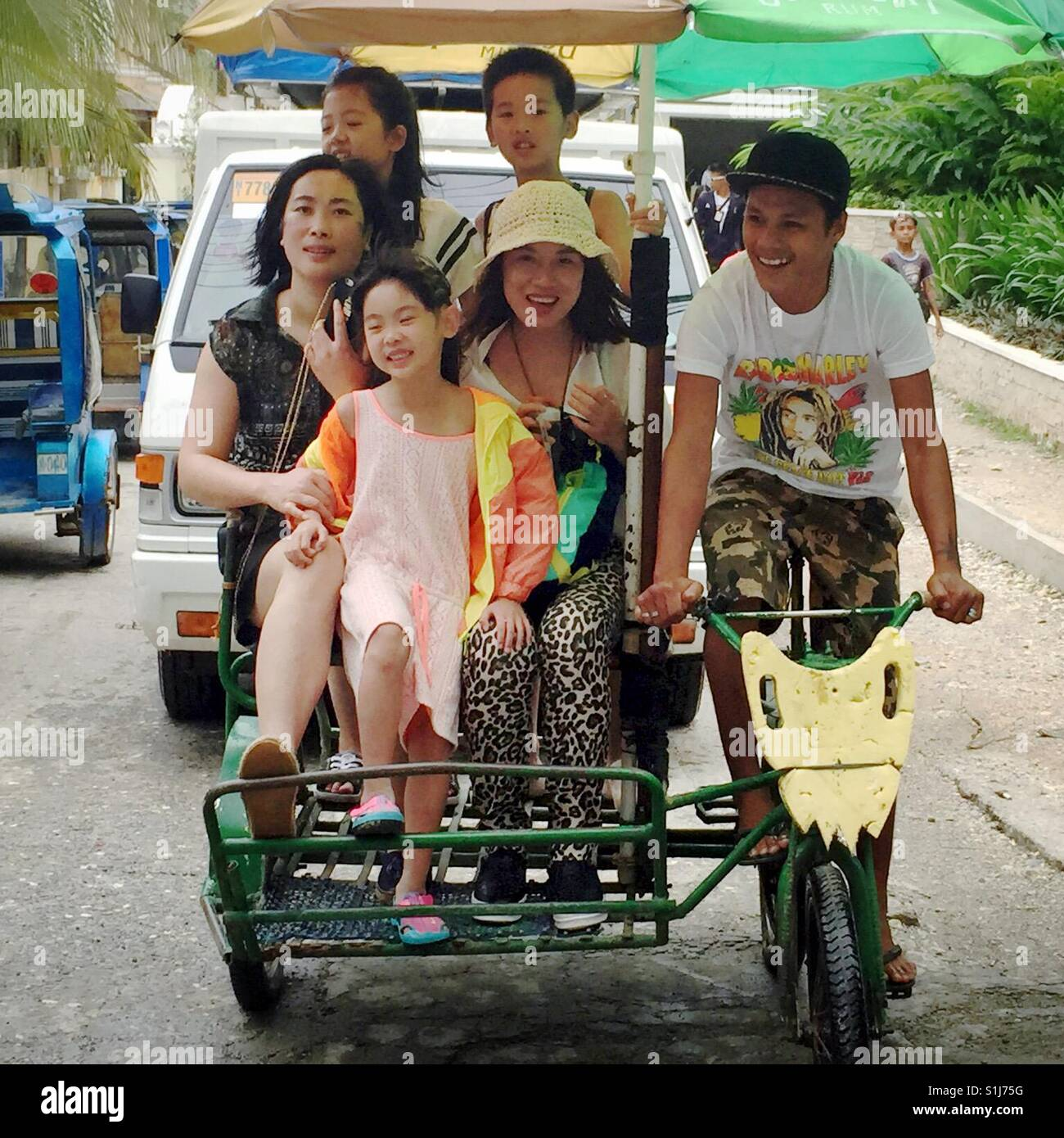 Group of happy people riding on a trike in Philippines - Stock Image