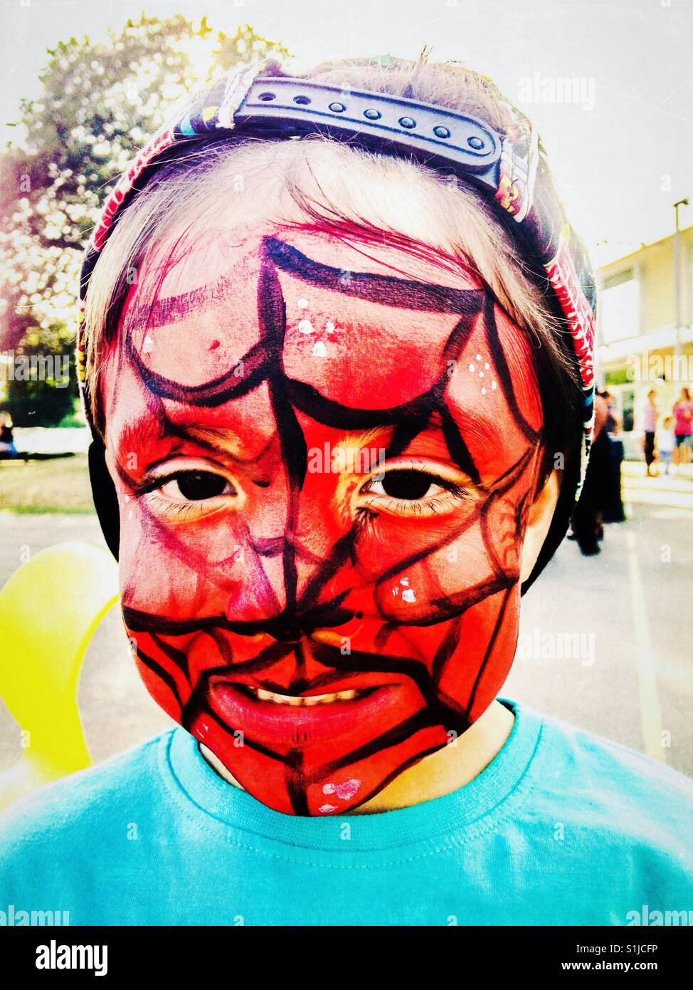 Portrait of a young boy wearing Spider-Man face paint. - Stock Image