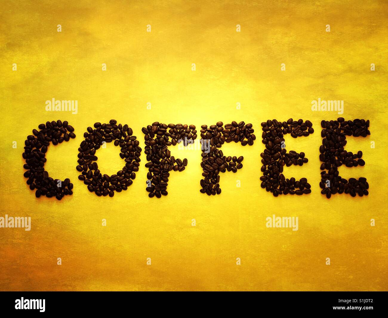 Coffee beans spelling out coffee on a yellow background - Stock Image
