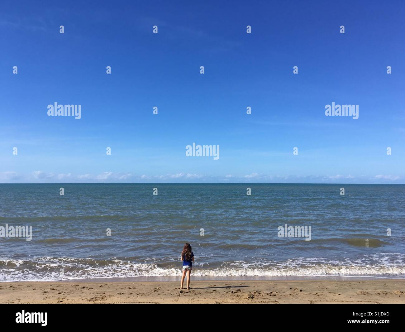 Little girl staring at the horizon on a beach. - Stock Image