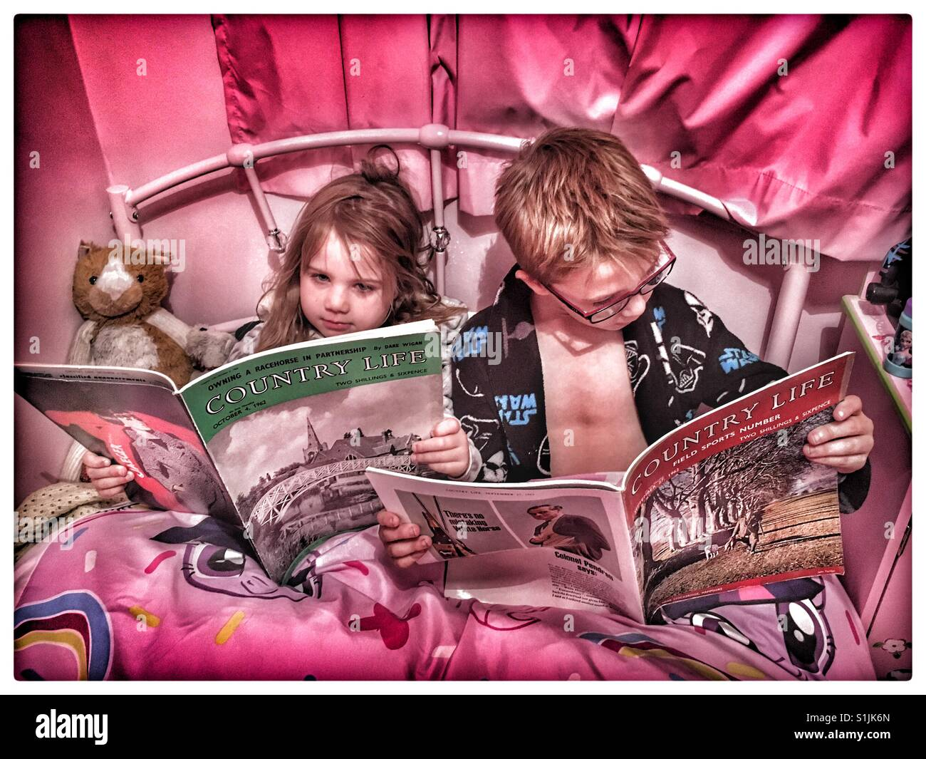 Brother and Sister reading vintage 1962 copies of Country Life before bed. - Stock Image