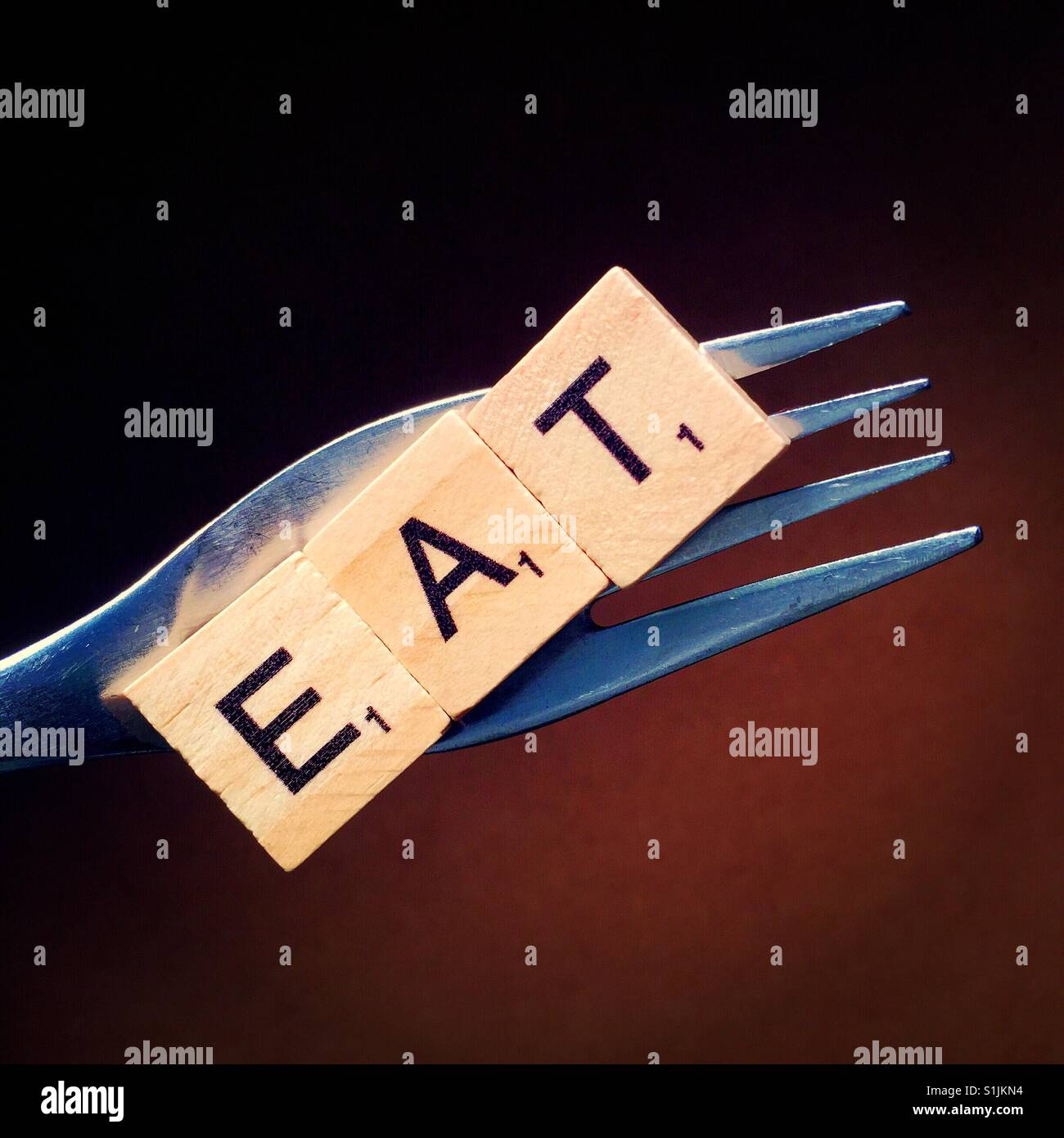 Close up of a fork with letters spelling eat on it - Stock Image