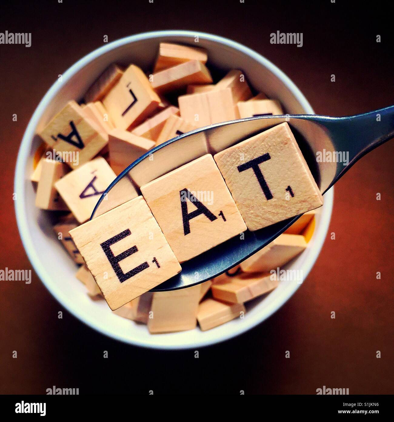 Close up of a spoon with wooden letters on it spelling out eat and a bowl full of wooden letters beneath it - Stock Image