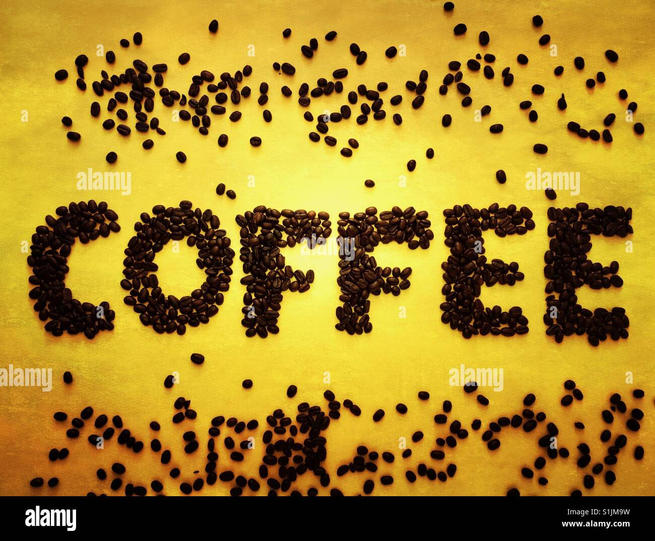 Coffee beans spelling out the word coffee on a yellow background Stock Photo