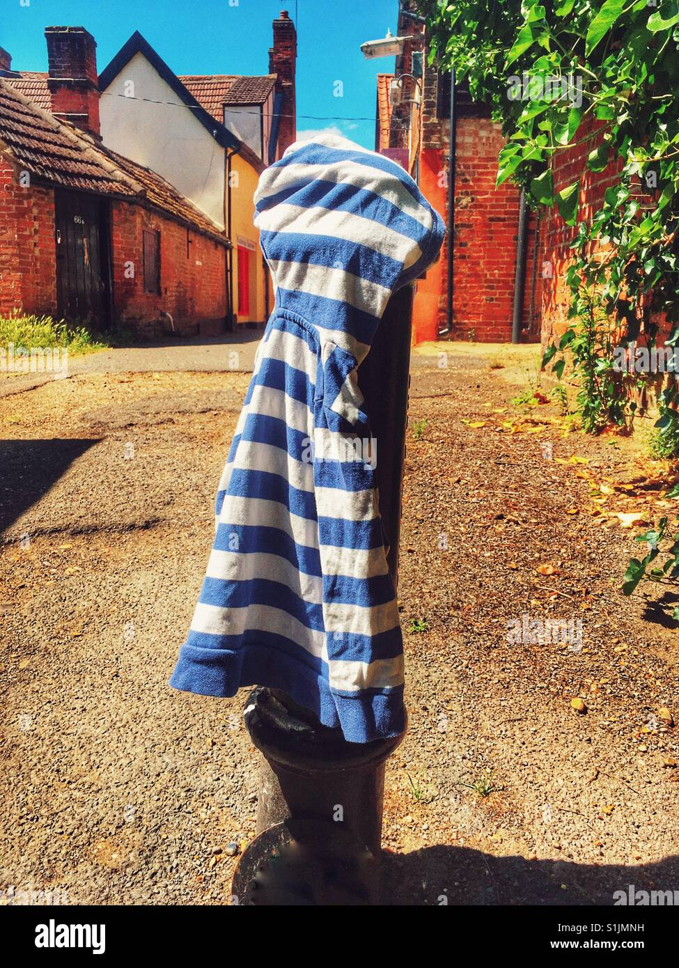 Child's hooded top lost and placed on post for owner to find, Woodbridge, Suffolk, UK. - Stock Image