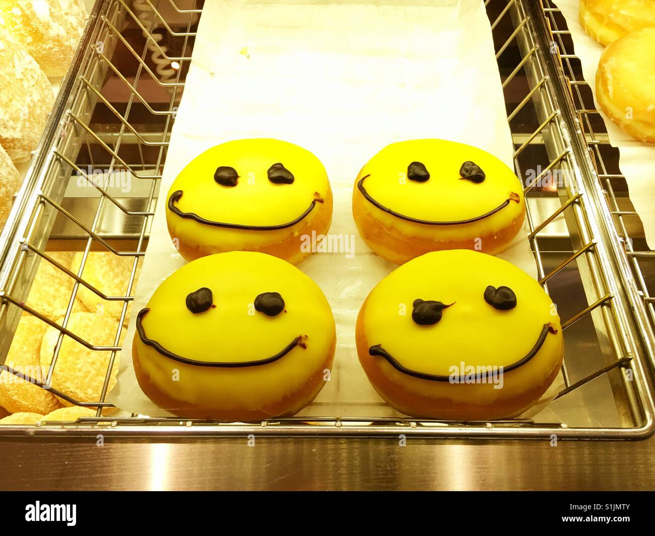 Smiling happy emoji donuts filled with Bavarian cream - Stock Image