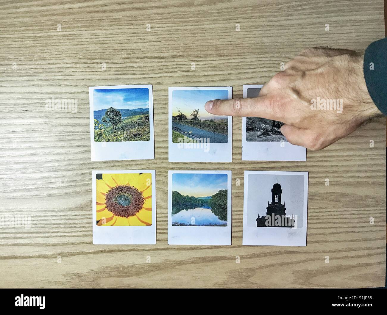Man's hand choosing a picture among 6 options over a wood tabletop - Stock Image