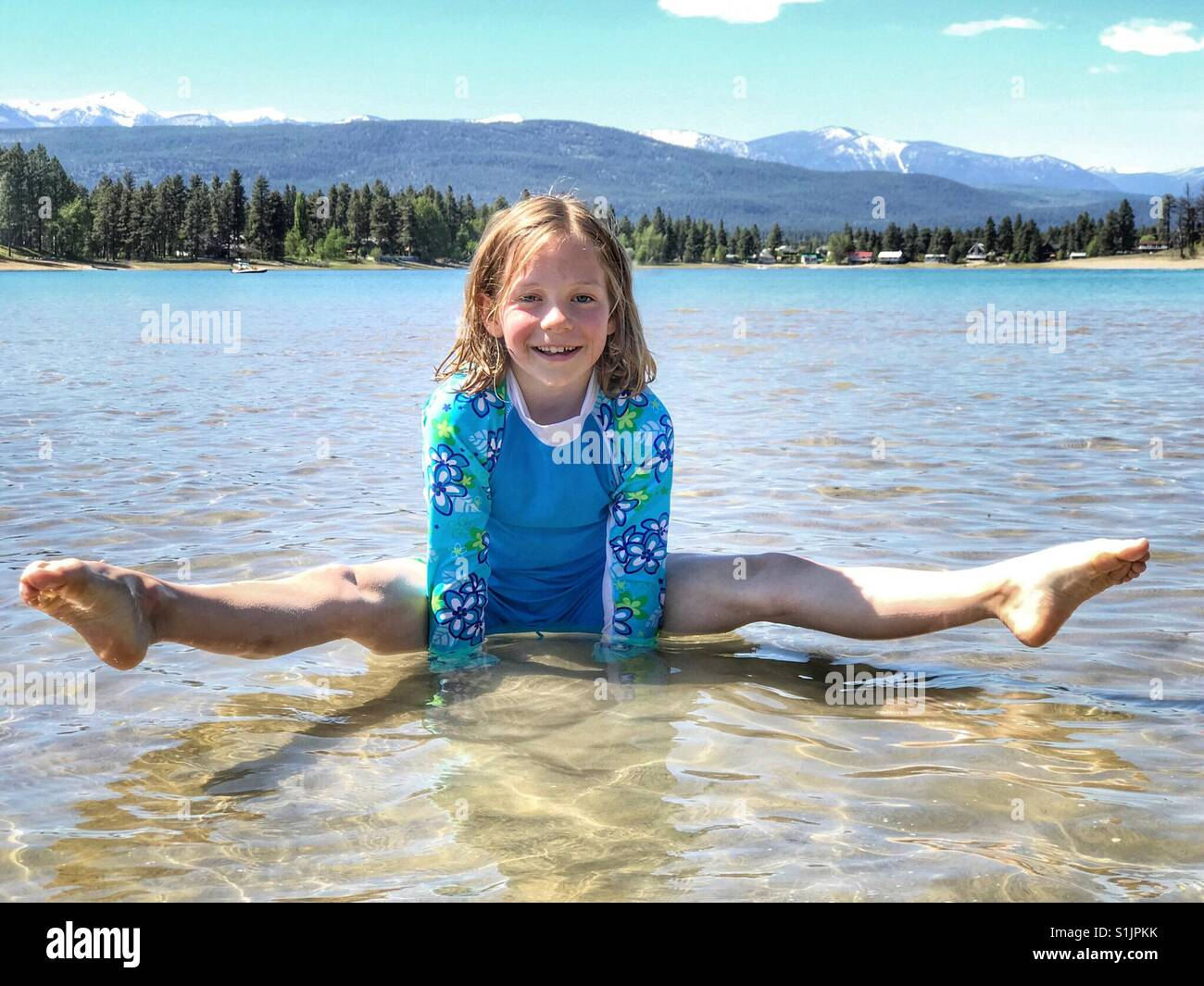 A girl balances on her hands in the shallows of a small lake. - Stock Image