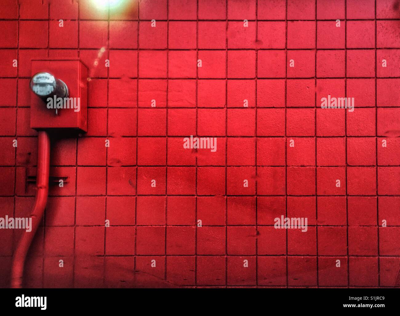 Red wall with electric meter - Stock Image