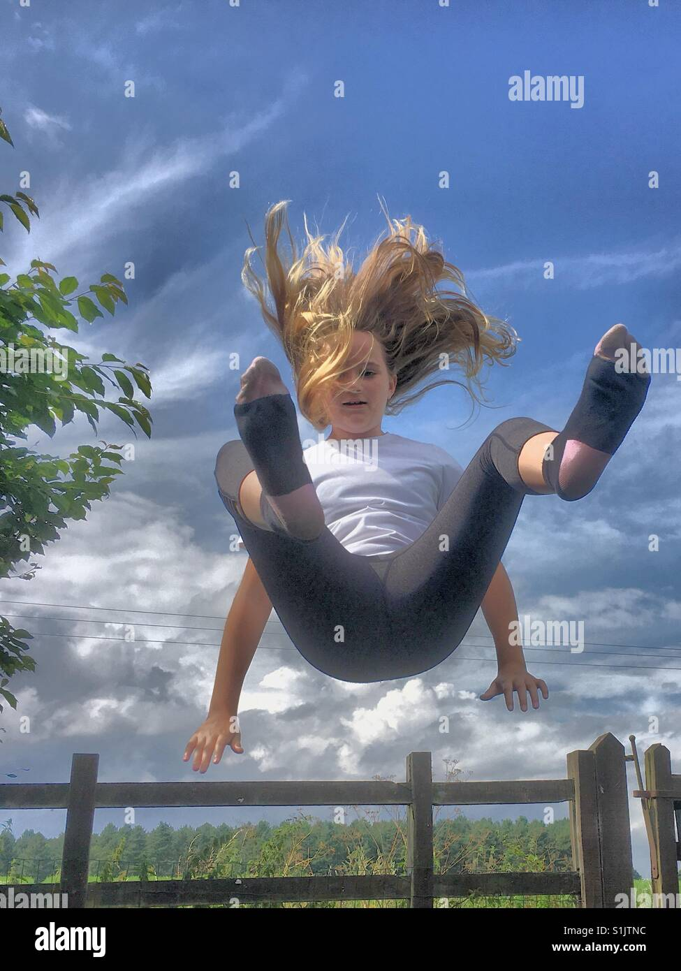 Girl bouncing on a trampoline outdoors - Stock Image