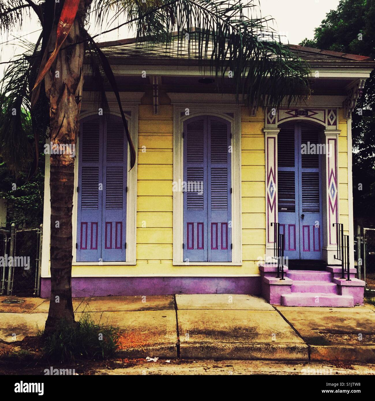 Yellow house with purple shades in New Orleans - Stock Image