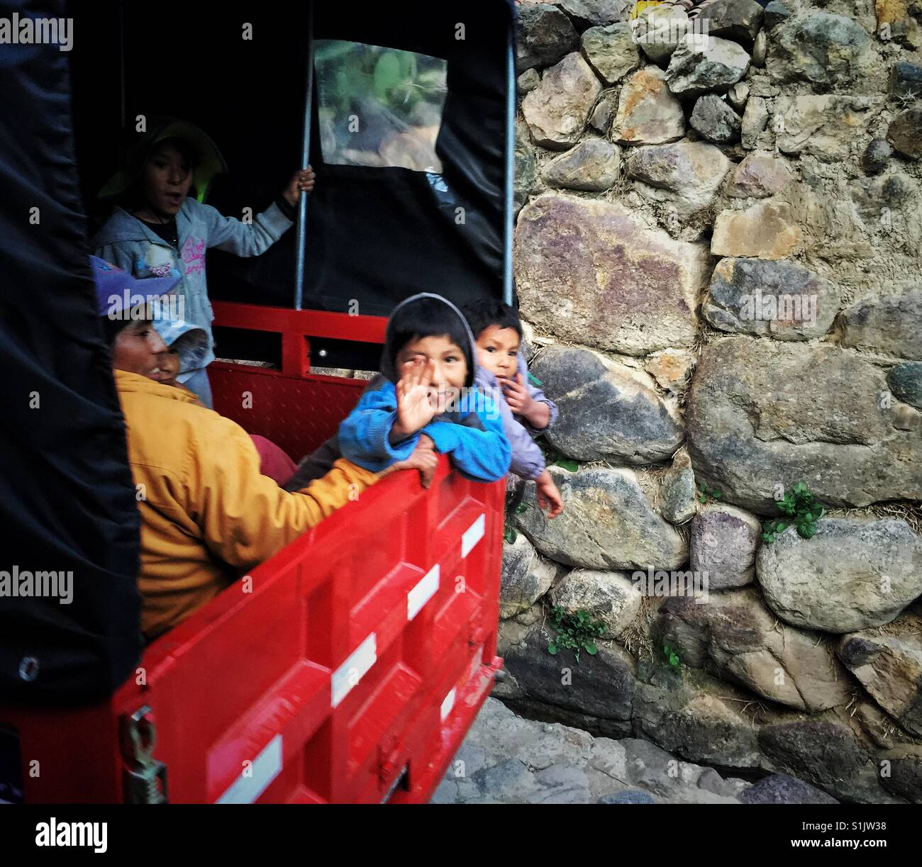 Red pickup truck full of children on a narrow street of Olantaytambo in Cusco region in Peru - Stock Image