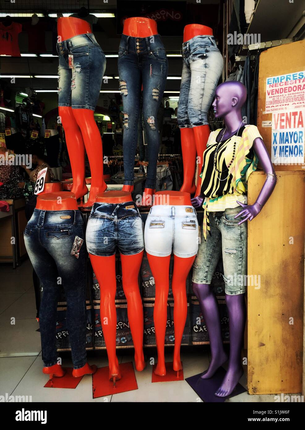Orange legs and purple female manikin modeling cheap jeans clothes in Lima, Peru - Stock Image
