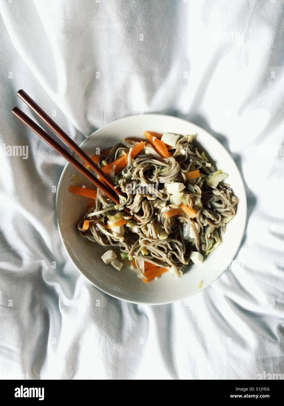 Round white bowl with soba noodles and vegetables with chopsticks on white crumpled bedding - Stock Image