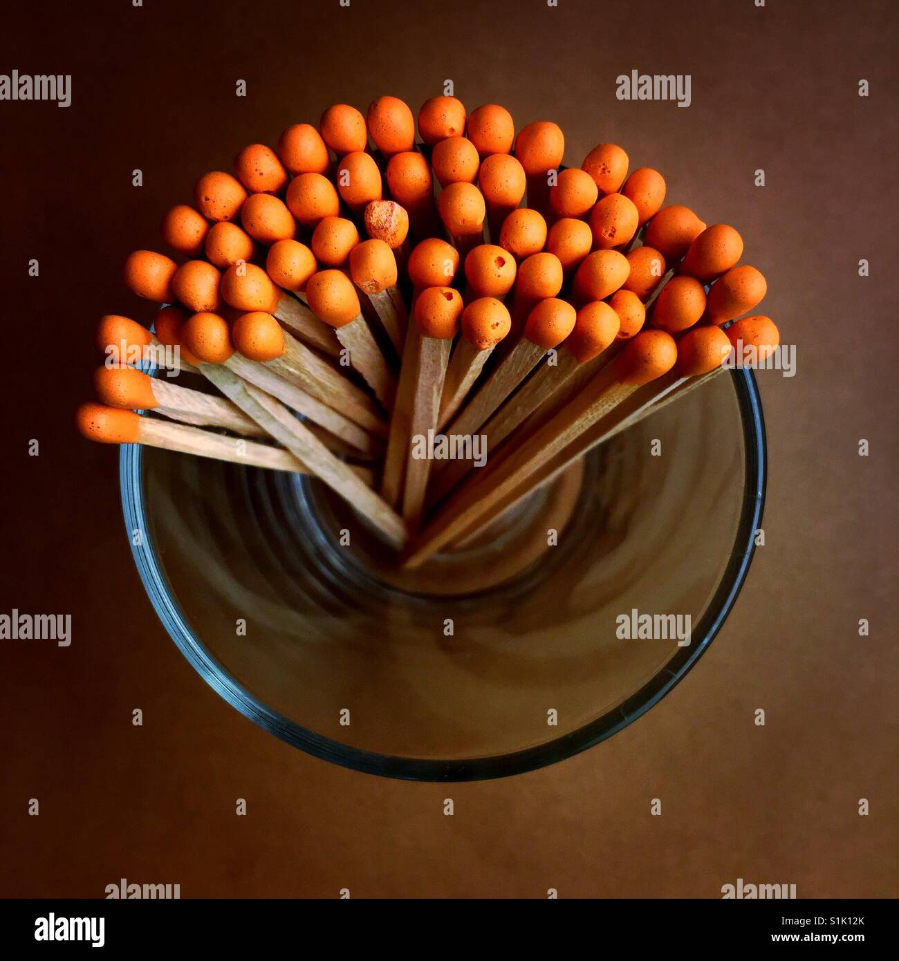 An overhead shot of a bunch of orange tipped matchsticks in a glass container - Stock Image