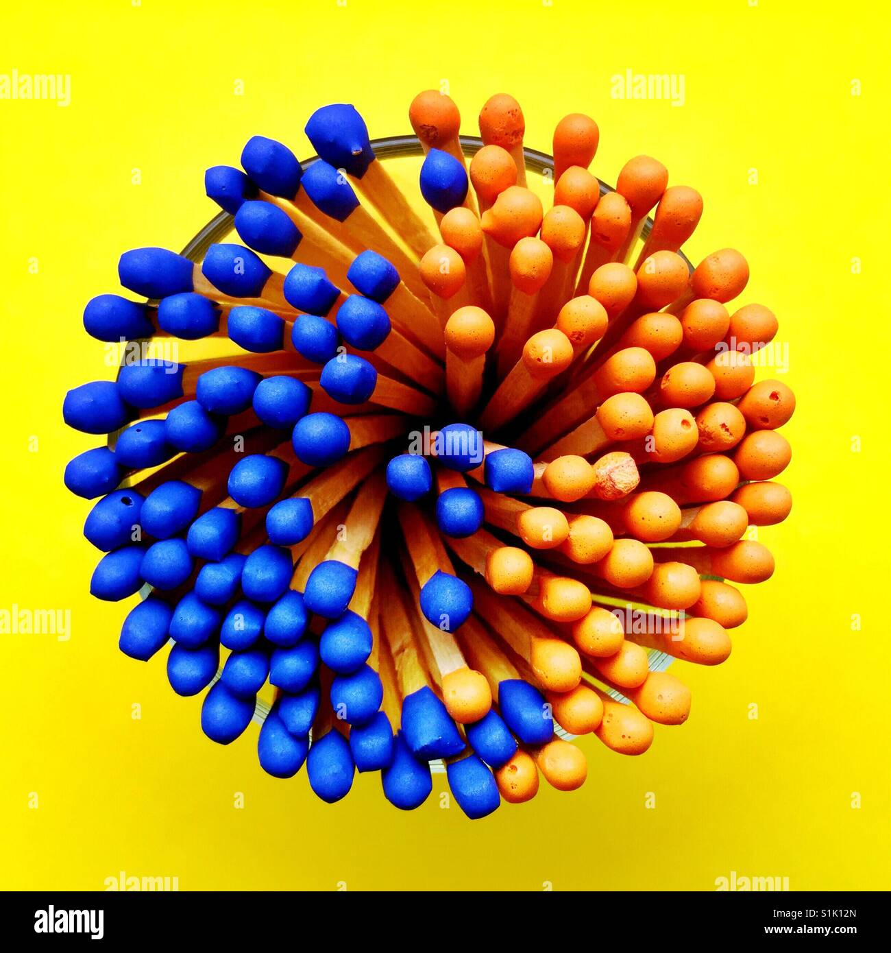 An overhead shot of a bunch of blue and orange tipped matchsticks in a glass container - Stock Image