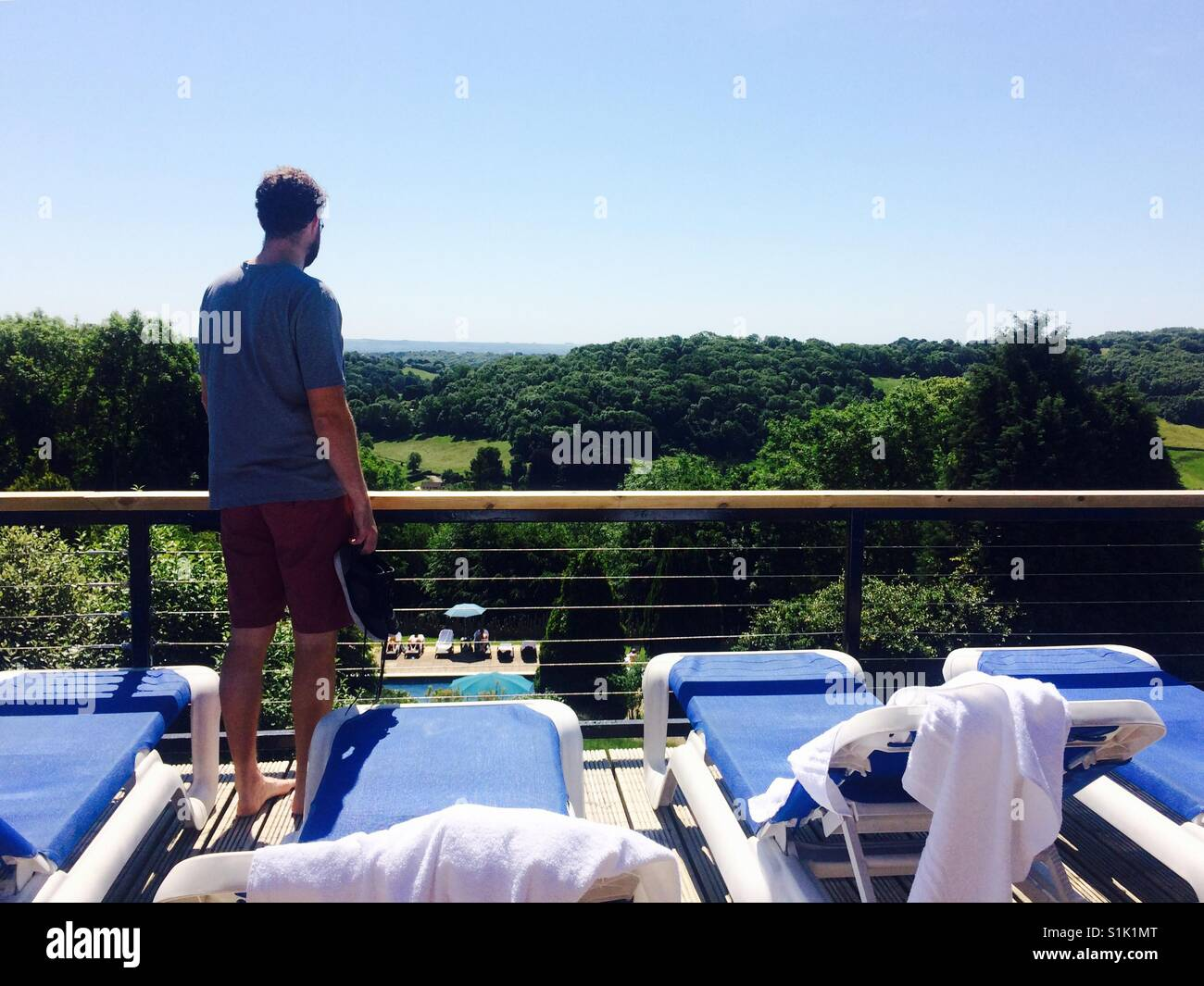 A man looks out from a hotel balcony surrounded by sun beds, in Bath Stock Photo