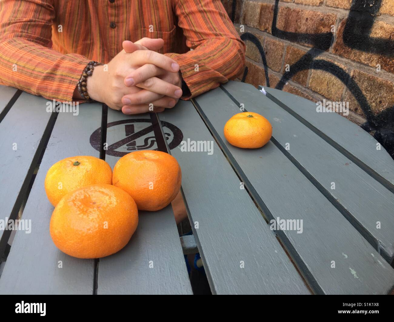 Oranges on a blue table and graffiti wall - Stock Image