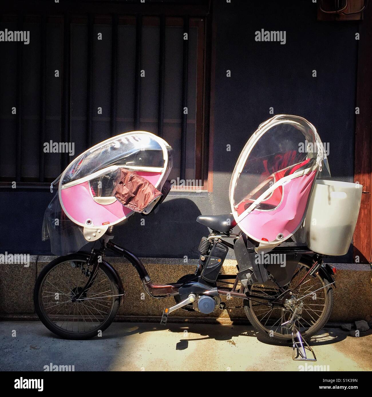 Street bicycle equipped with two pink covered child seats in front and back in residential area of Kyoto - Stock Image
