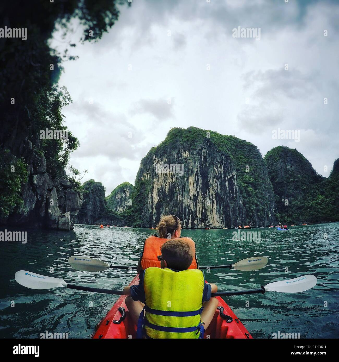 A family of an adult and child kayaking in the emerald waters of the Halong Bay in Vietnam. Limestone peaks topped - Stock Image