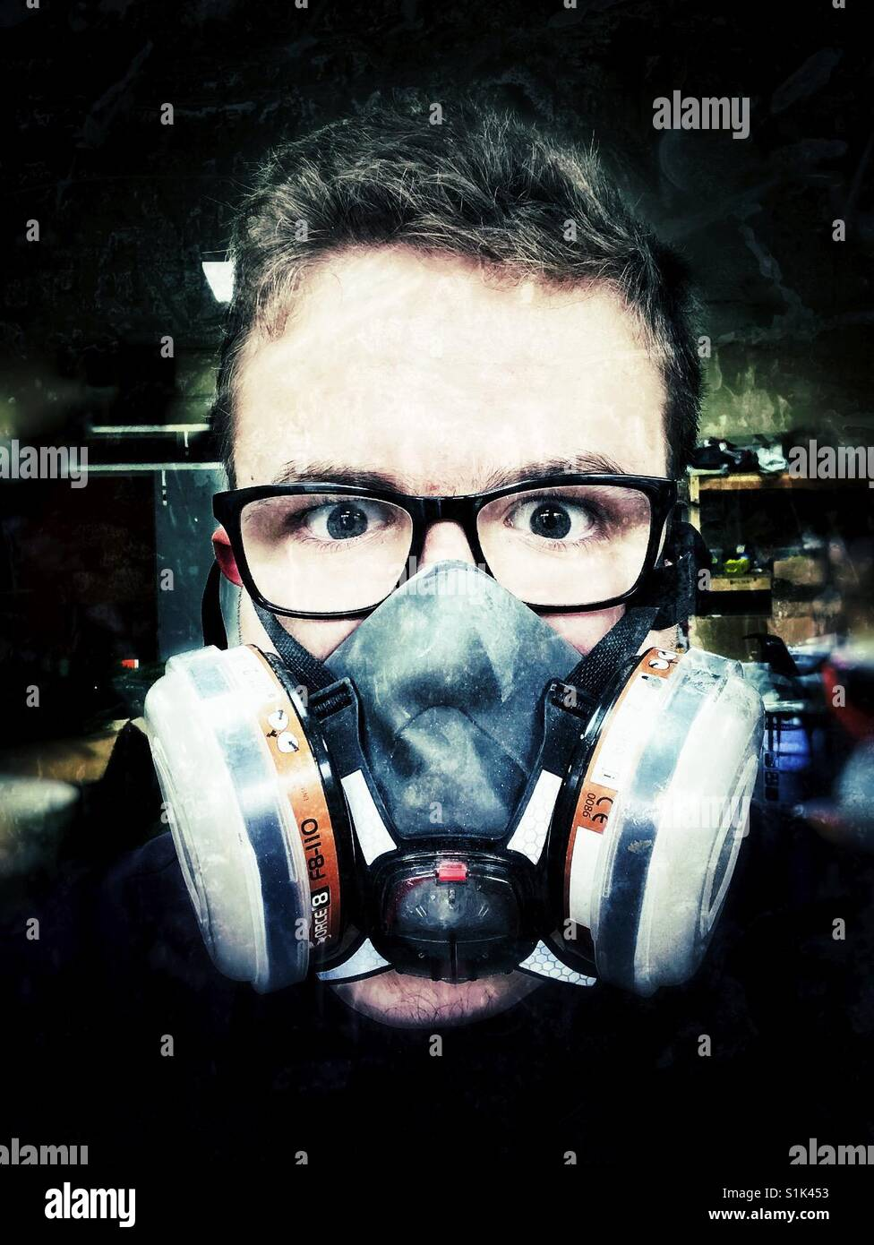 A young man wearing a breathing mask or respirator or gas mask - Stock Image