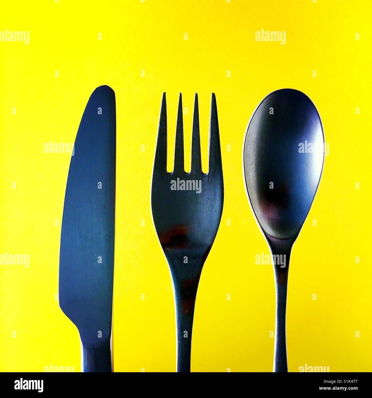 A close up overhead shot of a knife a fork and a spoon above a yellow background - Stock Image