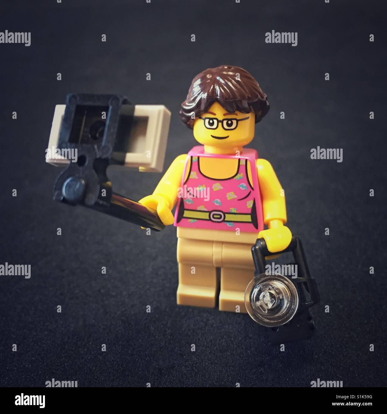 My LEGO likeness holding a selfie stick and camera - Stock Image