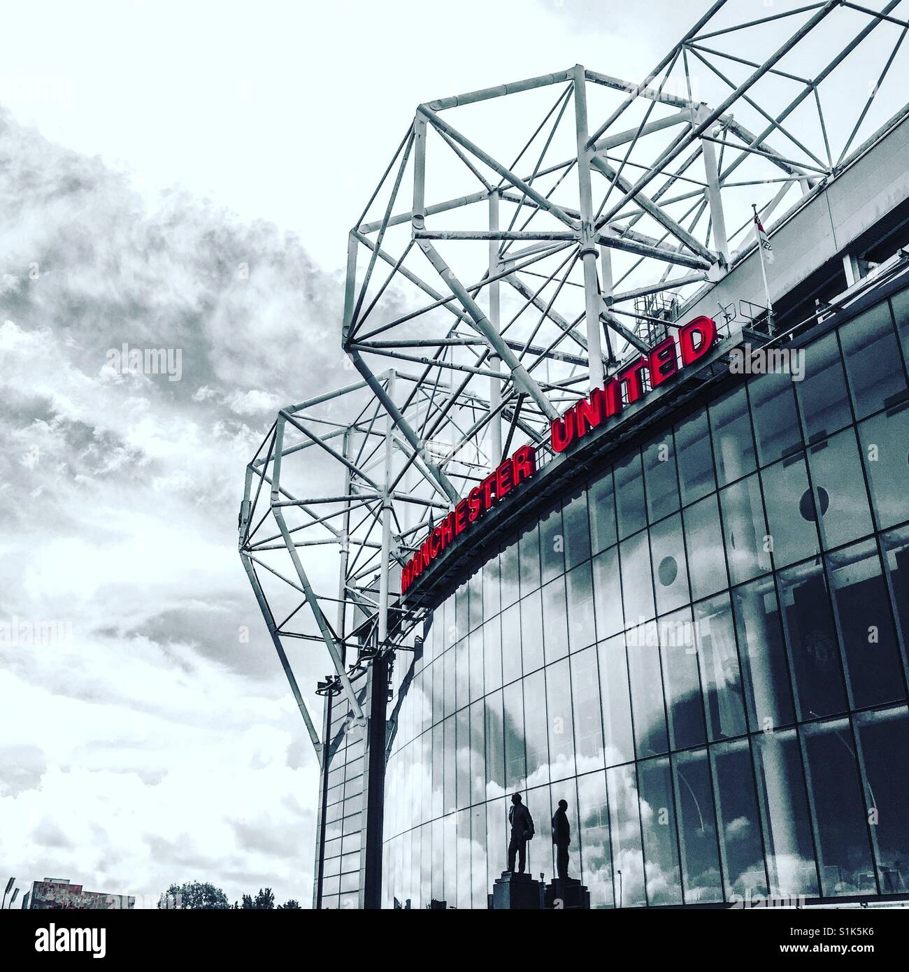 Front facade of Old Trafford, home of Manchester United, and the statue of its legendary manager Sir Matt Busby - Stock Image