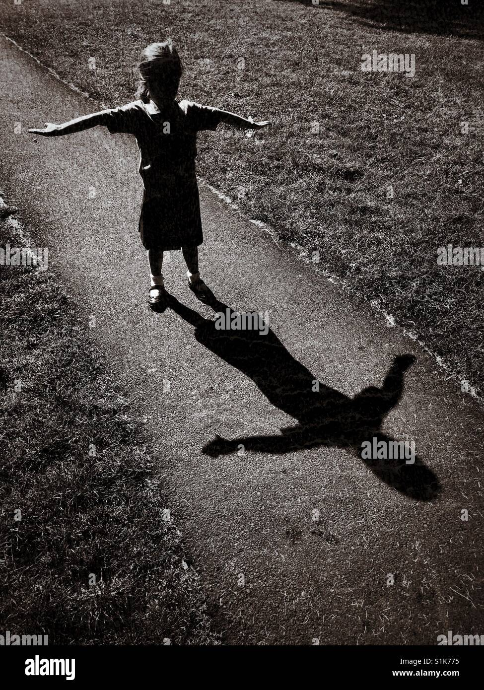 The shadow of a 5 year old child as she raises her arms and tries to create a 't' shape. A grunge effect - Stock Image