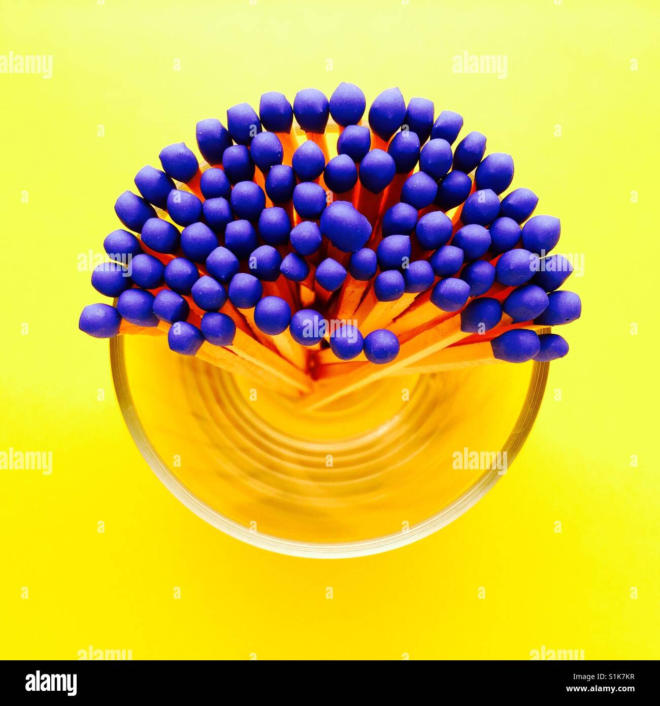 An overhead shot of a glass container half full of blue tipped matchsticks - Stock Image