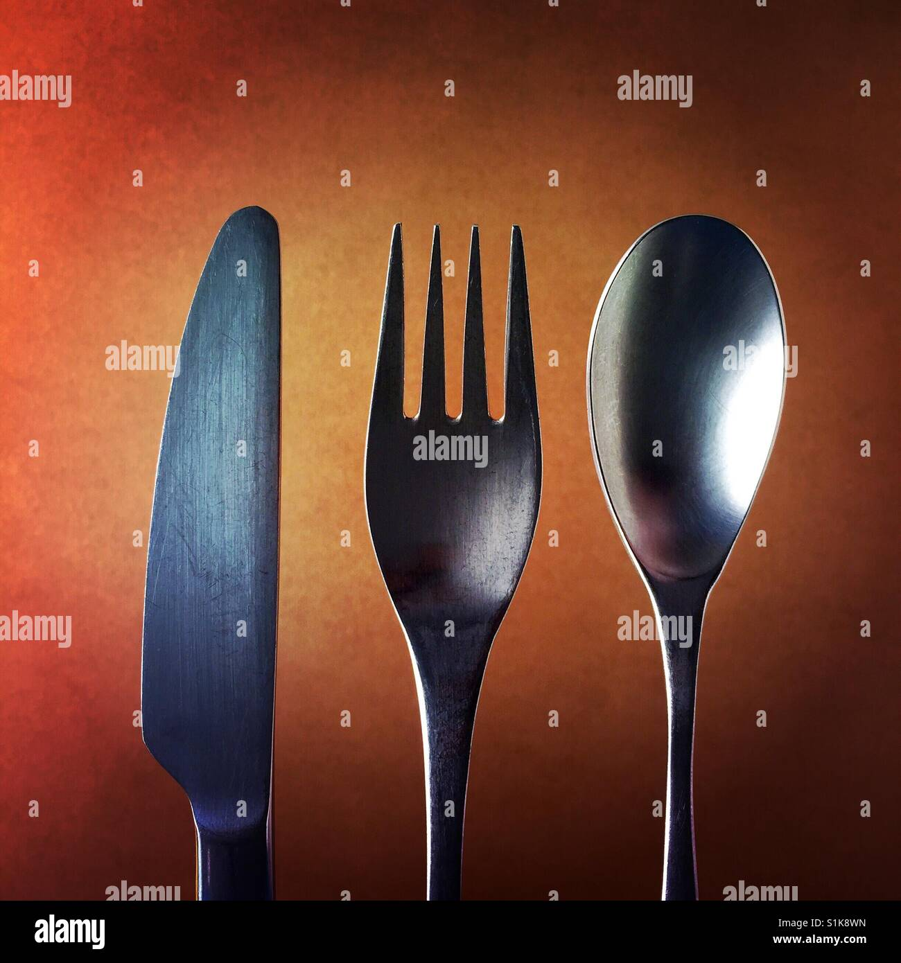 A close up shot of a knife and a fork and a spoon above a brown background - Stock Image