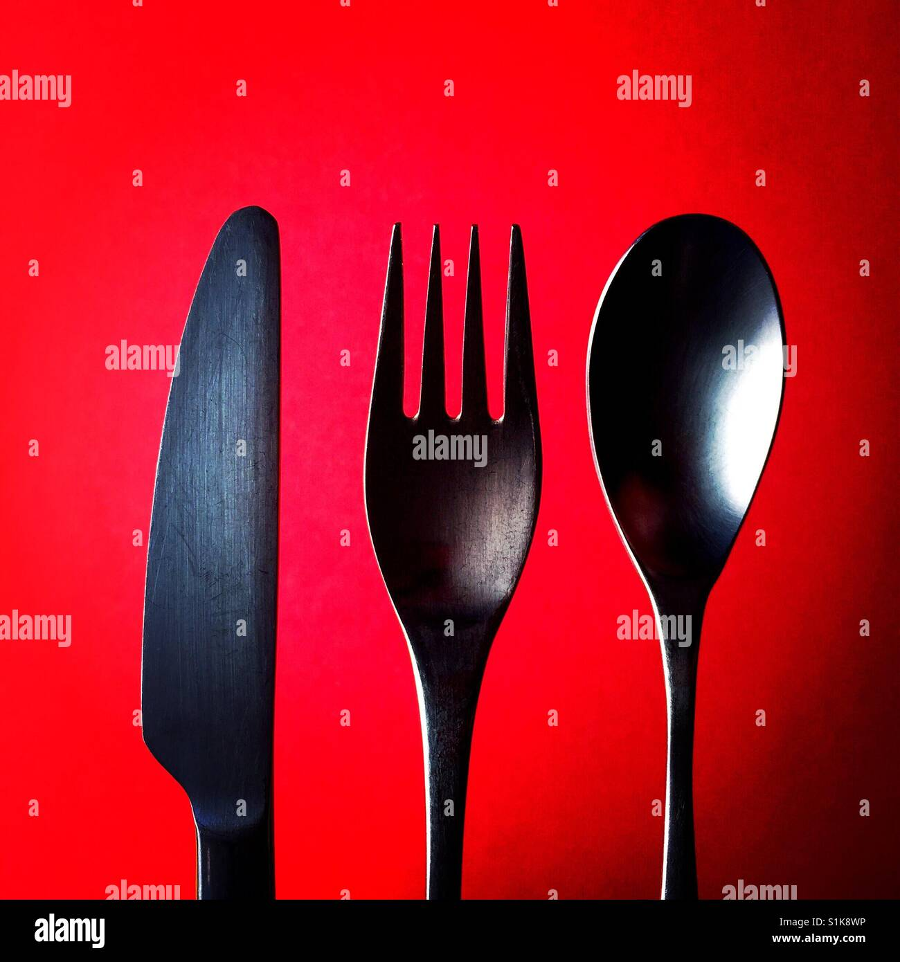 A close up overhead shot of a knife and a fork and a spoon above a red background - Stock Image