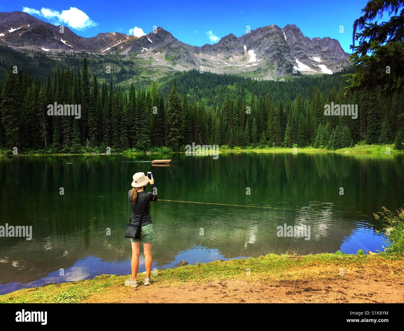 A young woman takes a picture of a beautiful mountain lake scene with her mobile phone - Stock Image