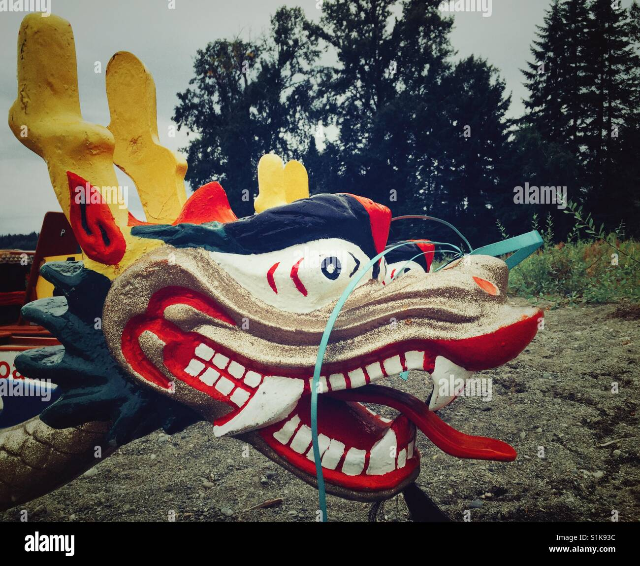 Carved and painted dragon head of a dragonboat on a neach - Stock Image