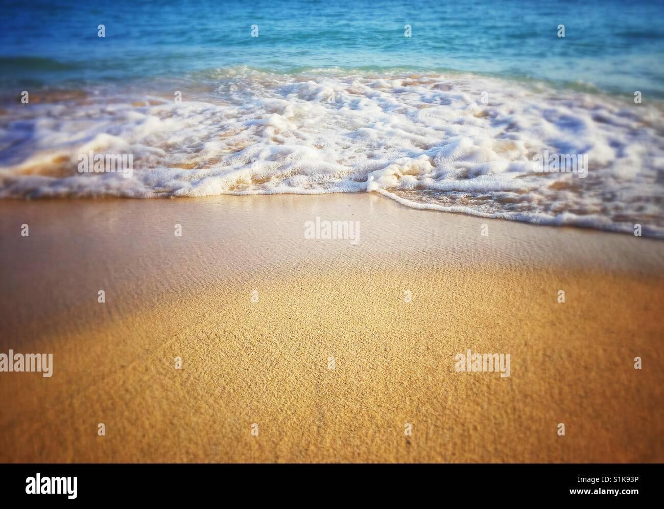 Wave breaks on beach. Foam swirl seascape on beach. Close up of wave foam on sand. - Stock Image