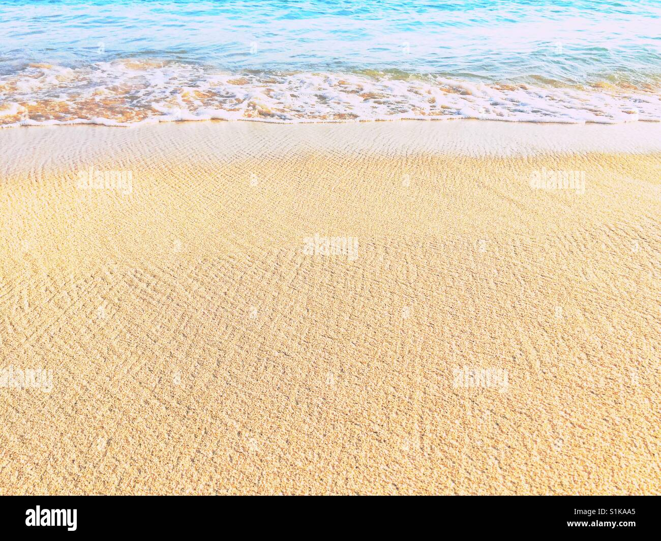 Texture patterns on the beach. Low angle perspective of surf on sand - Stock Image