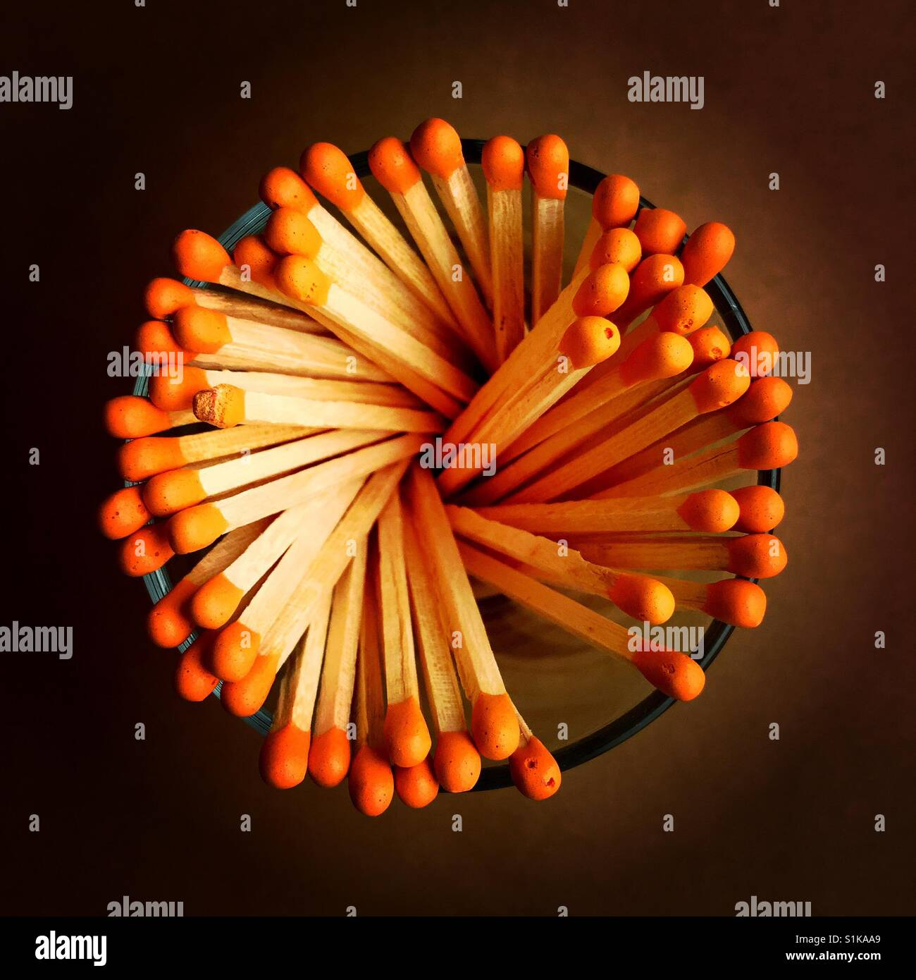 An overhead shot of a bunch of matchsticks in a glass container - Stock Image