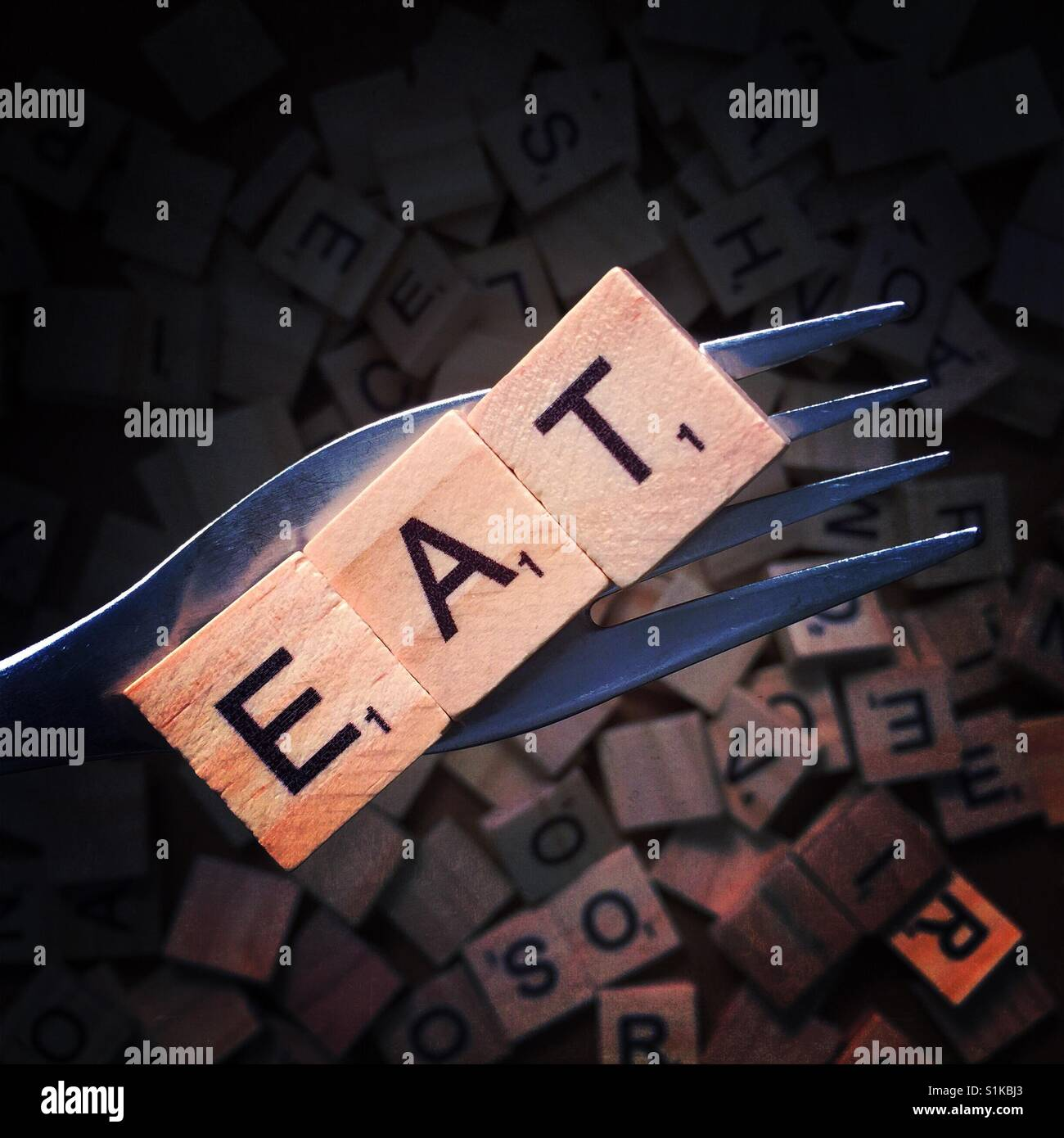 Close up of a fork with wooden letters on it spelling eat above a background with more wooden letters - Stock Image