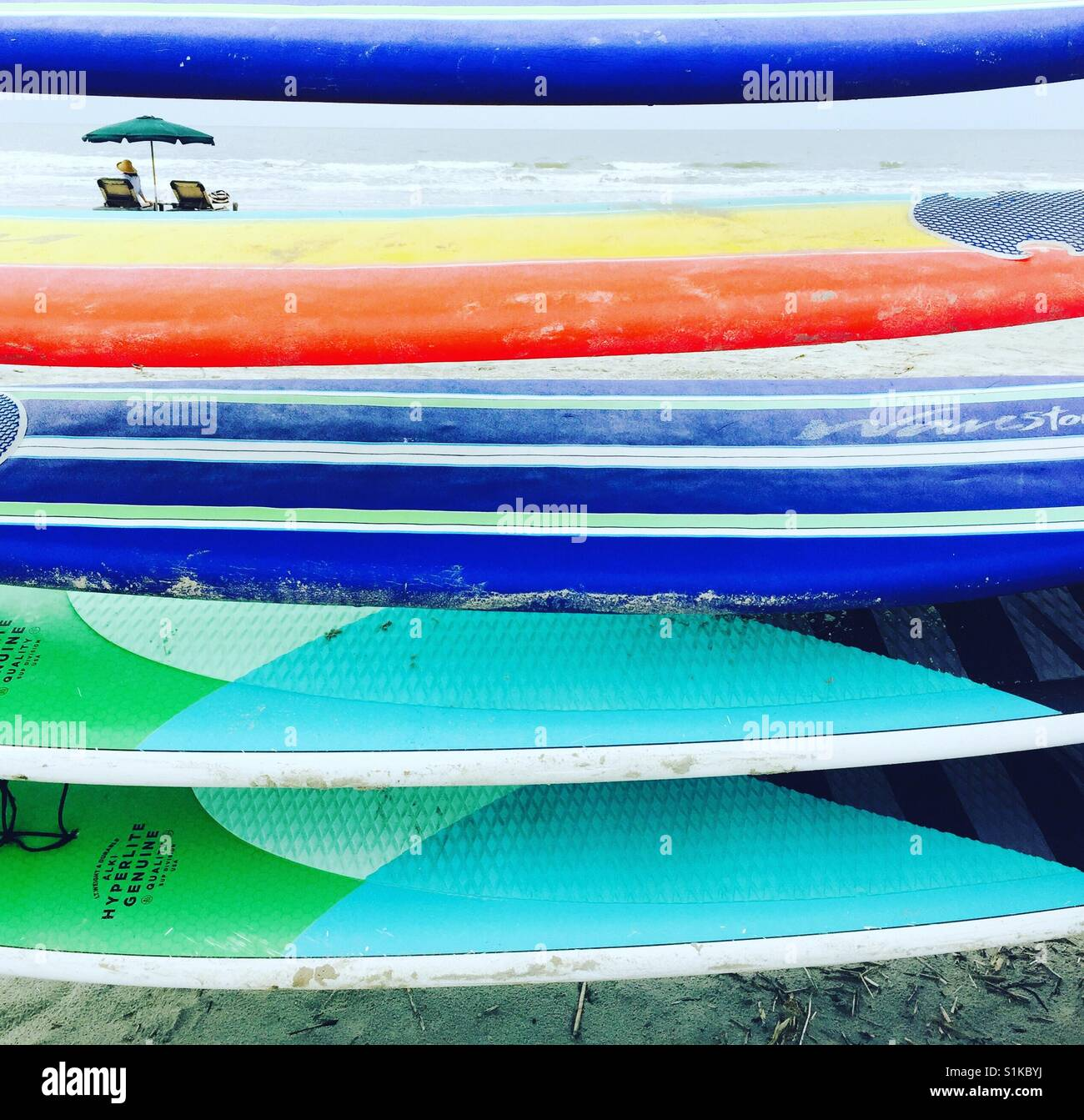 A stack of colorful surf boards and paddle boards. - Stock Image