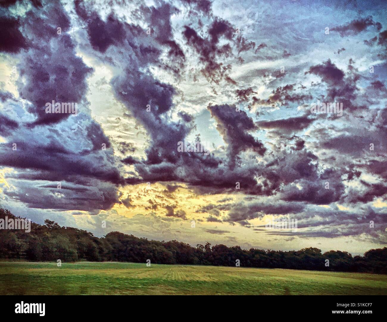 Beautiful sun rise behind dark clouds - Stock Image