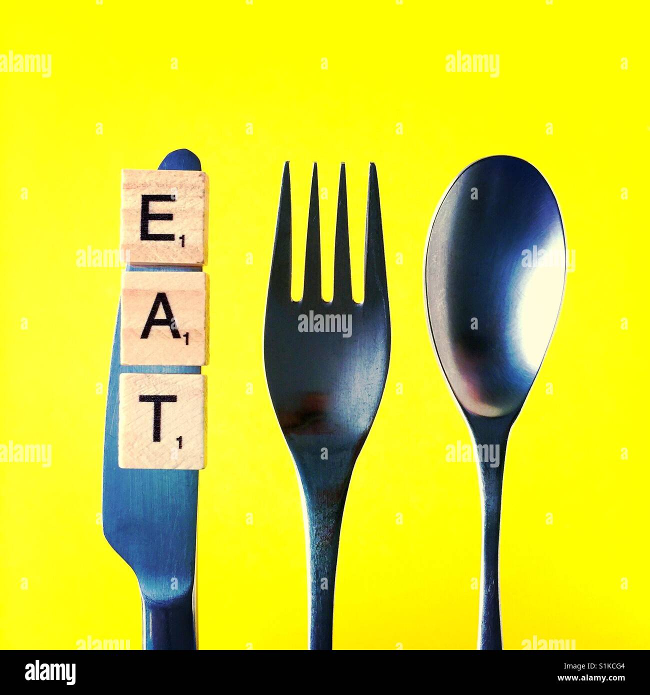 A close-up overhead shot of a knife and a fork and a spoon above a yellow background with the word eat on the knife - Stock Image