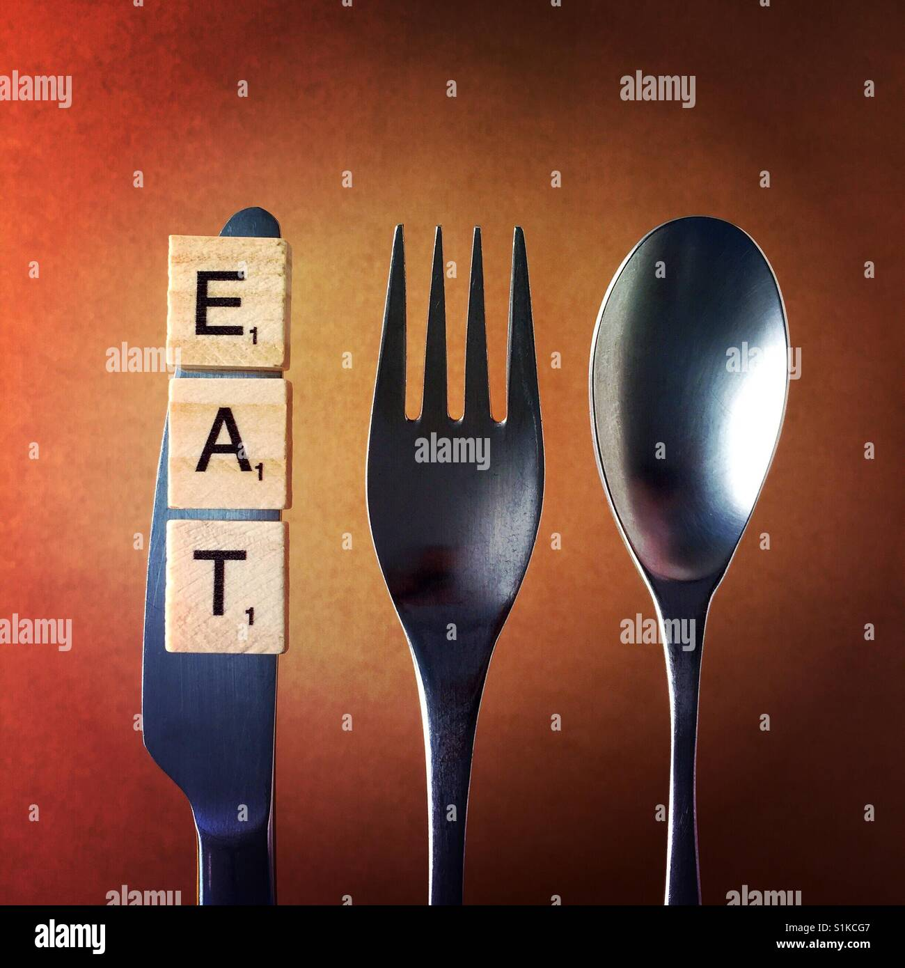 A close up overhead shot of a knife and a fork and a spoon above a brown background with the word eat on the knife - Stock Image