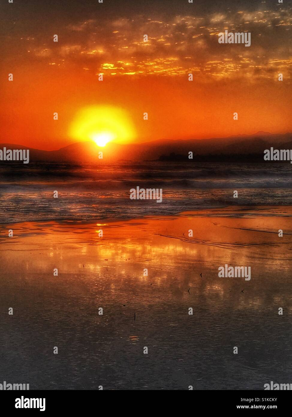 Sunset seascape at Pismo beach, California. View from beach across ocean as sunset behind headland. Golden colours - Stock Image