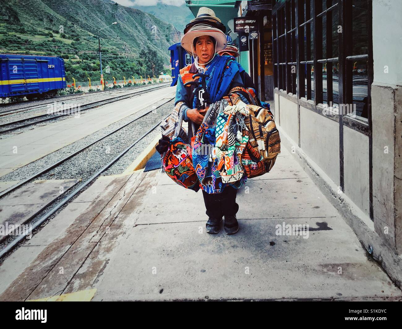 Peruvian traditional textile seller carrying his goods on a train station in Ollantaytambo - Stock Image