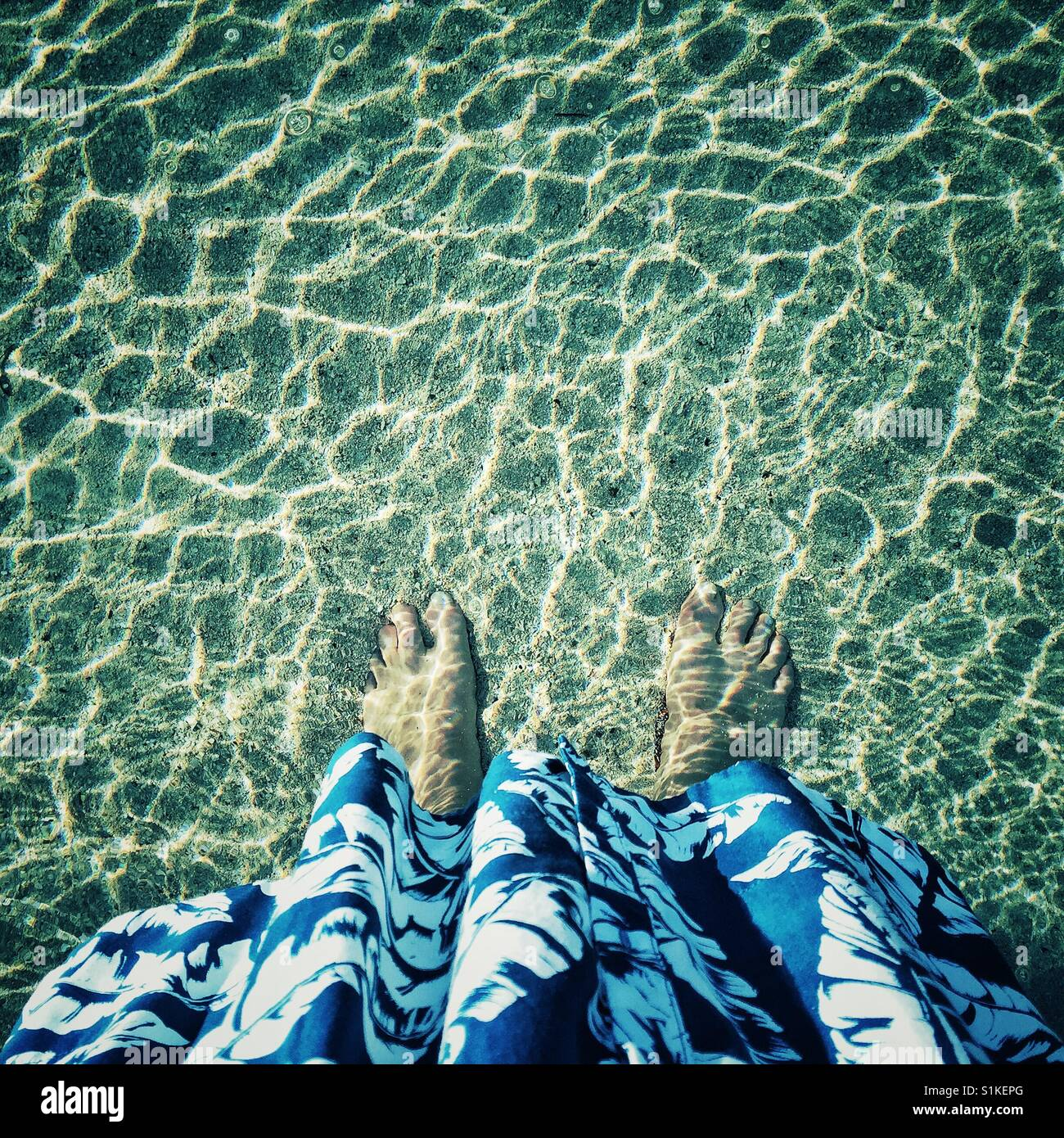 Tropical dress and bare feet in glimmering ocean - Stock Image