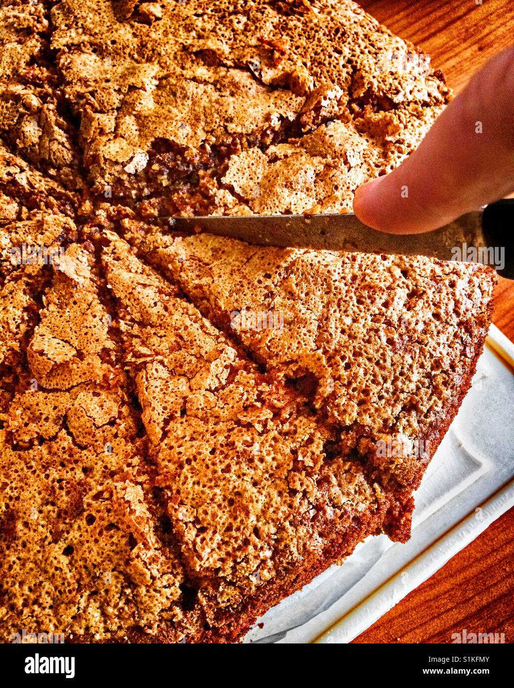 Woman hand with knife cutting homemade carrot cake - Stock Image