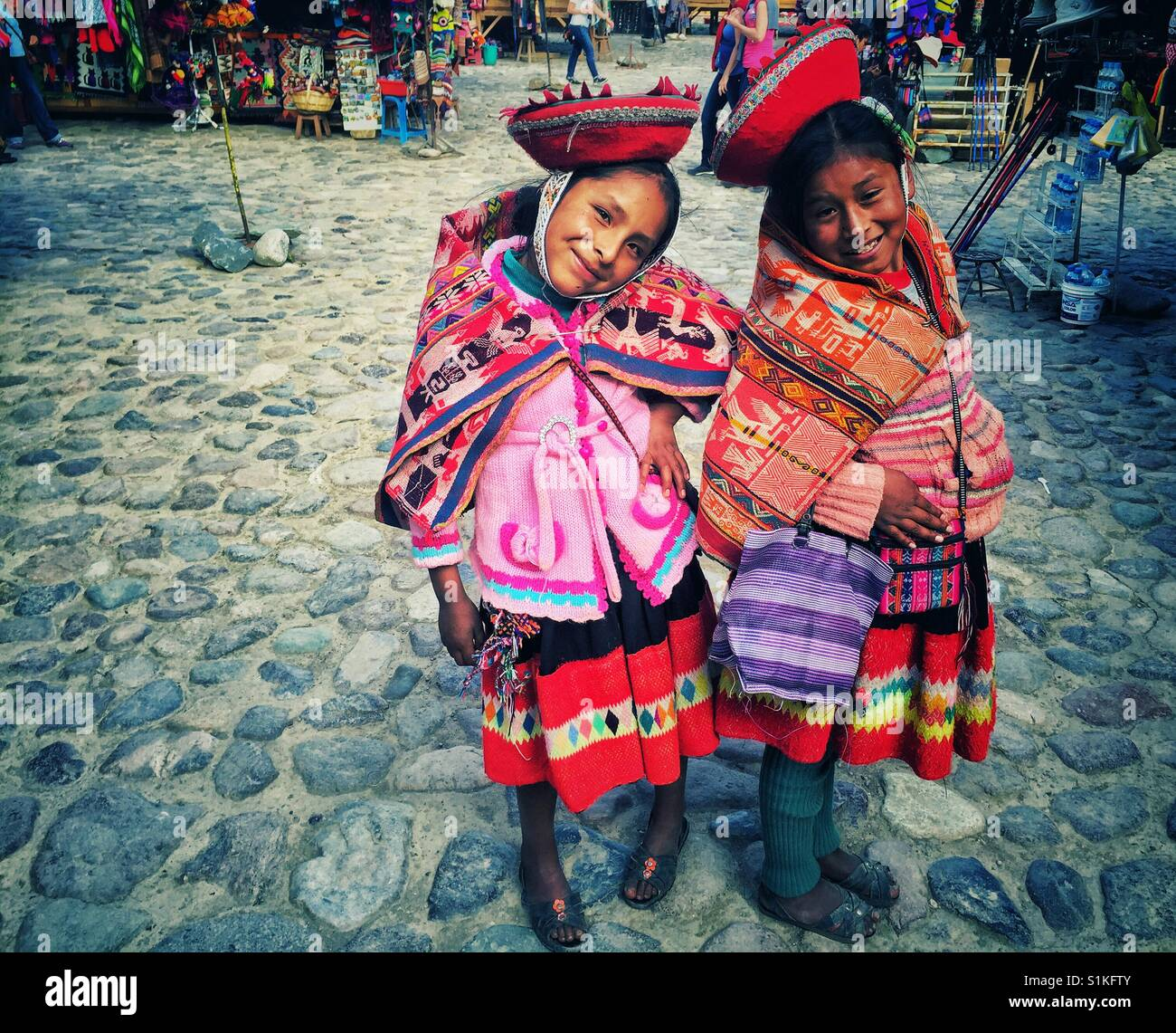 Two young Peruvian girls in traditional clothes posing and smiling for the camera in Ollantaytambo - Stock Image